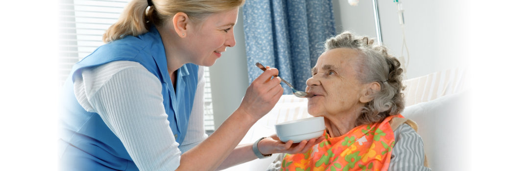 caregiver feed the elderly woman